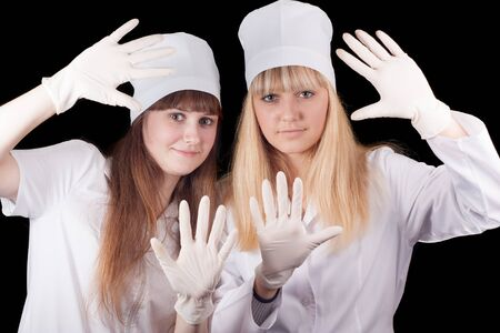 Two nurses wear protective gloves on a black background Stock Photo - 16758070