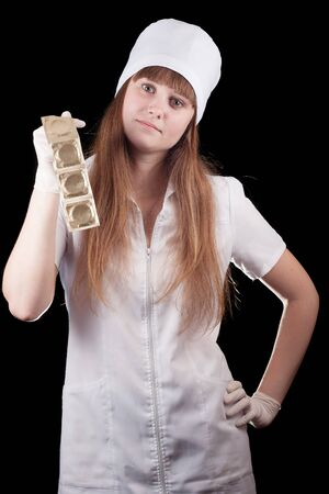 Nurse in uniform hold condoms on a black background  Stock Photo - 16757932