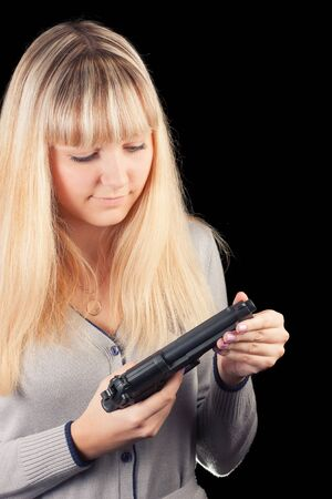 A young girl on a black background with a gun  Stock Photo - 16758083