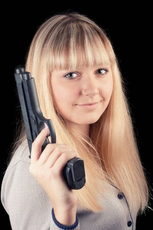 A young girl on a black background with a gun Stock Photo - 16758084