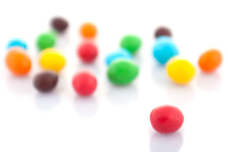 Multicolored round candies on a white background  The shallow depth of field  Stock Photo
