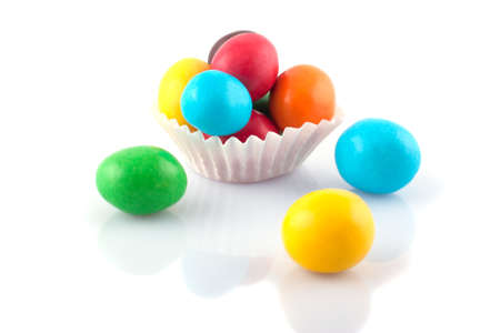 Multicolored round candies in paper basket on a white background   Stock Photo