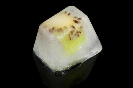 Slice of kiwi fruit frozen in ice on a black background