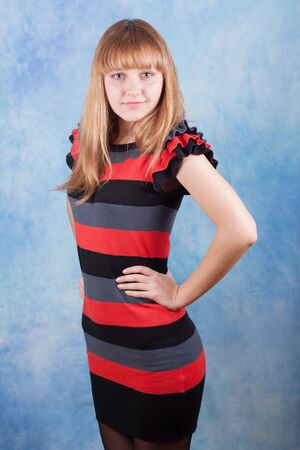 Beautiful girl in a striped dress on a blue background  Stock Photo