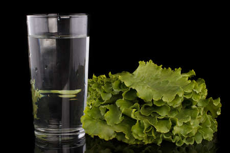 Fresh lettuce leaves next to a glass of water on a black background