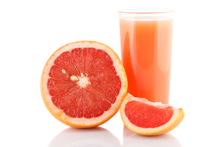 Glass of grapefruit juice and grapefruit slice isolated on white