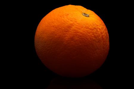 One orange on a black background