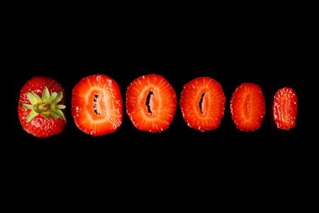 Beautiful sliced strawberries on a black background