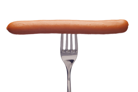 eating meat: Tasty sausage on a silver fork on a white background.