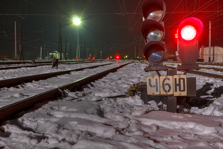 Railway traffic signal at the station at night in winter.