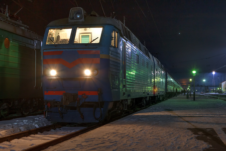 intercity: Old intercity train stops at a station in the winter night.