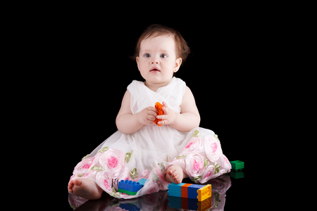 The girl is one year in dress sitting on a black background. photo