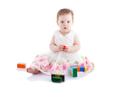 baby facial expressions: The girl is one year in dress sitting on a white background.