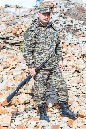 bombed: Military camouflage with a rifle on a background of bombed buildings.
