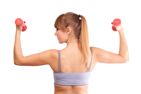 The girl goes in for sports with dumbbells on a white background.