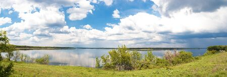 Bright, beautiful panorama of of the river on a sunny day with clouds. Stock Photo