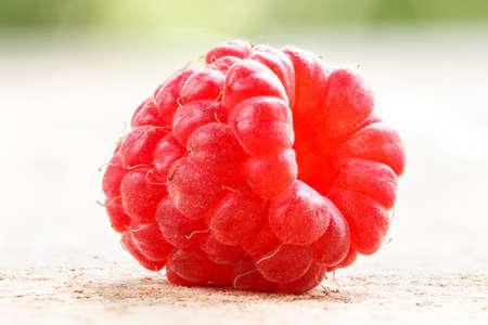 One ripe raspberry on background.