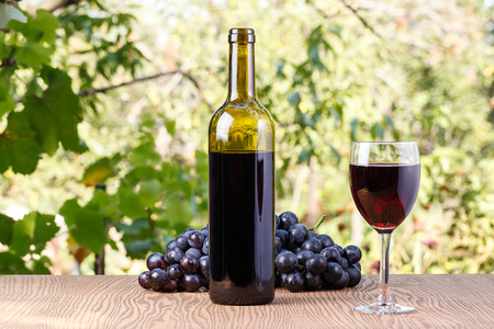 Bottle and a glass of wine with grapes on a wooden background outdoors. Stock Photo