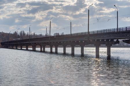 Photo of an industrial bridge through an artificial reservoir in the city.
