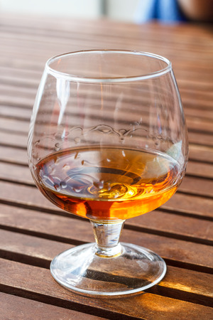 Glass of cognac standing on a wooden table in sunlight. Stock Photo