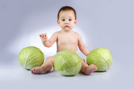 Beautiful little baby on a white background with green cabbage. Stock Photo