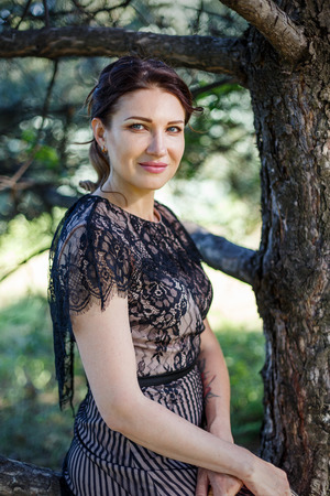 Portrait of a beautiful girl in a lace dress in a park. Фото со стока