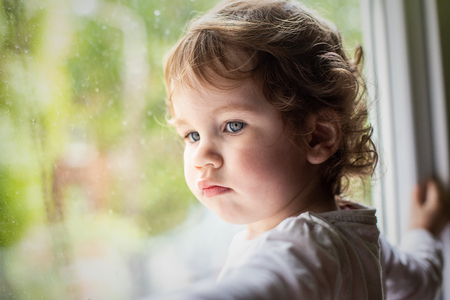 Photo of a little curly girl on the window sill, it is raining outside the window.