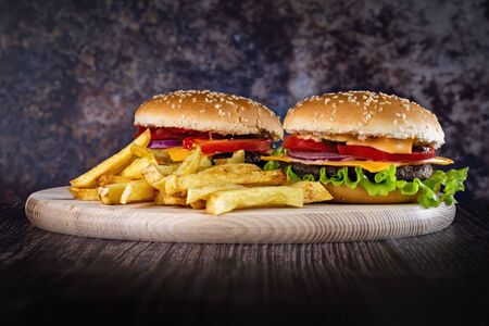 Photo of delicious burgers with fries with ketchup on a beautiful background. Фото со стока