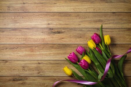 Tulips of different colors on a wooden background.  免版税图像