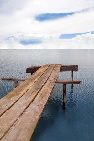 seawater: Wood bridge under the sky at an ocean.