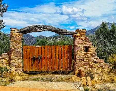Nice rural stone door with a crossbar trunk and the mountains in the background