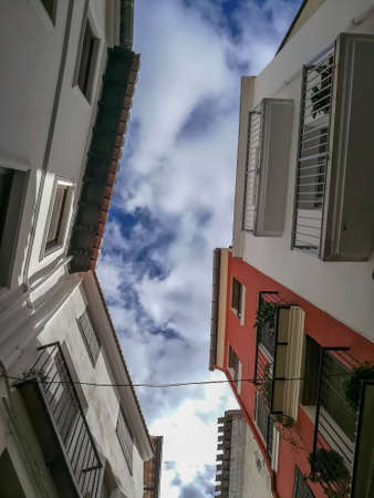 View from below of buildings with clouds sky