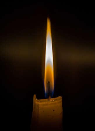Fiammiferi che bruciano per accendere una candela su sfondo nero