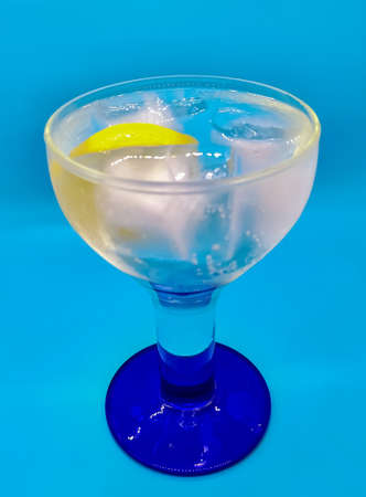 Gin and tonic with a slice of lemon on blue background