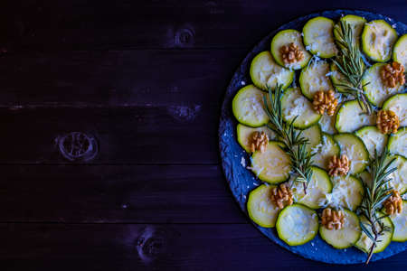 Carpaccio of zucchini with nuts and cheese on dark wooden background