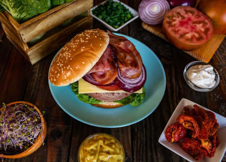 Hamburger and ingredients in composition on wooden background
