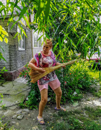 Woman pretending to play the guitar with a handmade broom
