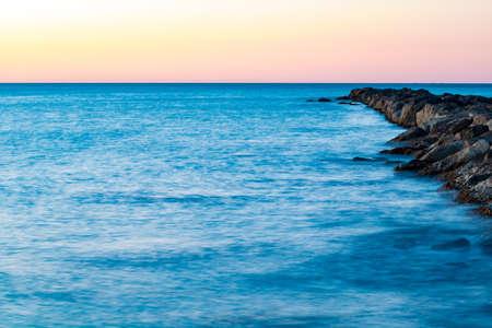Breakwater at Burriana beach in long exposure Stock Photo
