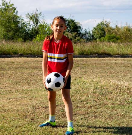 Little girl playing soccer on grassy esplanade Reklamní fotografie