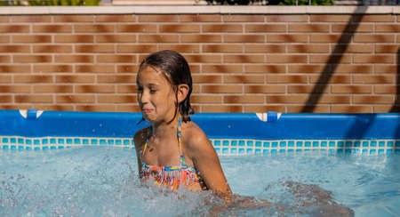 Little girl playing happily in the pool Imagens - 127830467