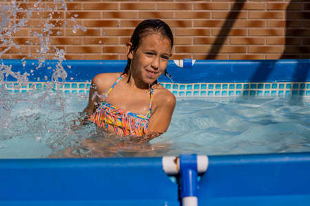 Little girl playing happily in the pool
