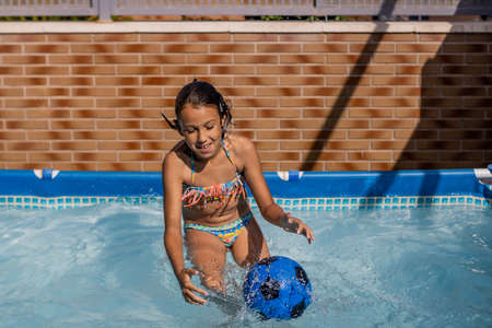 Little girl playing happily in the pool Imagens - 127830477