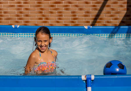 Little girl playing happily in the pool Imagens - 127830492