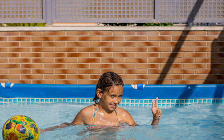 Little girl playing happily in the pool Imagens - 127830590