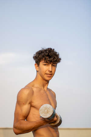 Young boy doing fitness without shirt at sunset Imagens - 128789493