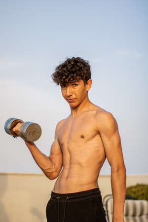 Young boy doing fitness without shirt at sunset Imagens - 128789496