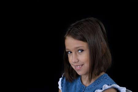 Little girl posing on black background Stock Photo