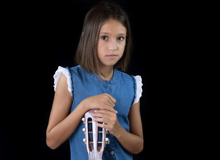 Small girl playing guitar on black background Imagens - 128789502