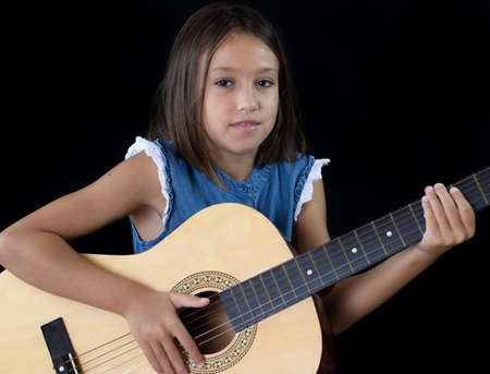 Small girl playing guitar on black background Imagens - 128789506