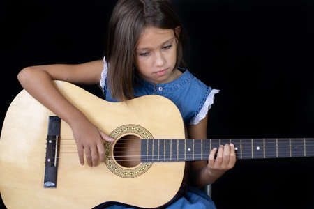 Small girl playing guitar on black background Imagens - 128789505
